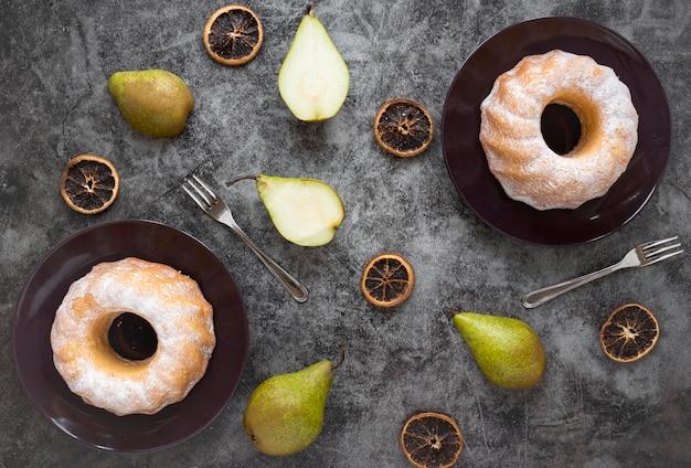Disposizione piana di ciambelle su piatti con pere e agrumi secchi