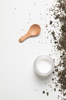 Disposizione piana di crema e cucchiaio su fondo bianco