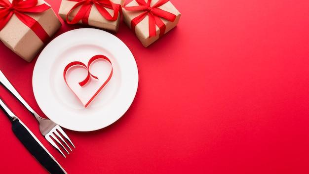 Disposizione piana di forma di cuore di carta sul piatto con lo spazio della copia