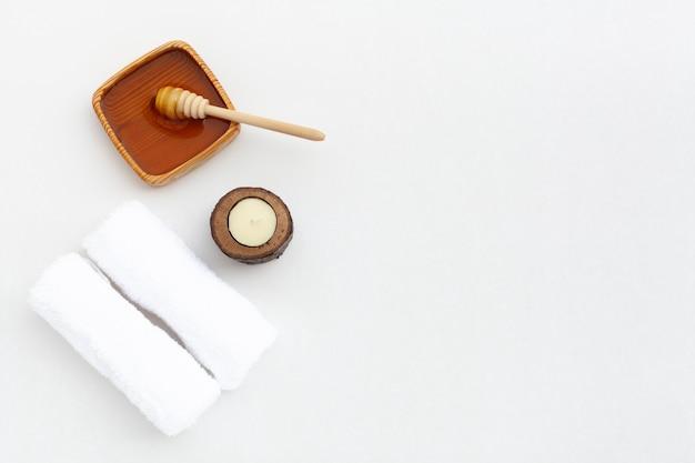 Disposizione piana di miele e stoffa su sfondo chiaro