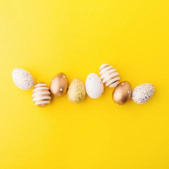 Disposizione piana di pasqua di uova su giallo