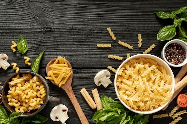 Disposizione piana di pasta e basilico sulla tavola di legno