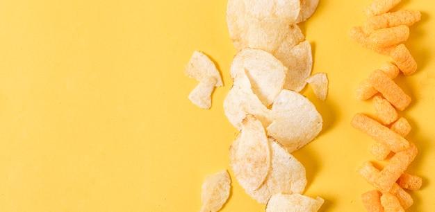 Disposizione piana di patatine fritte e sbuffi di formaggio con spazio di copia