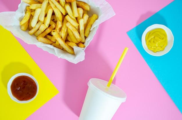 Disposizione piana di patatine fritte e soda su sfondo colorato