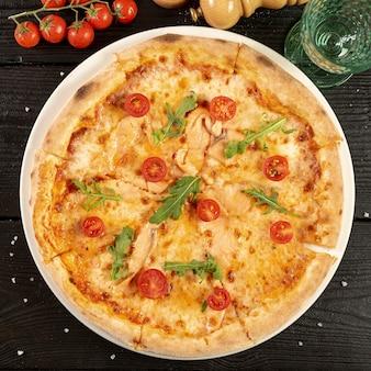 Disposizione piana di pizza deliziosa sulla tavola di legno