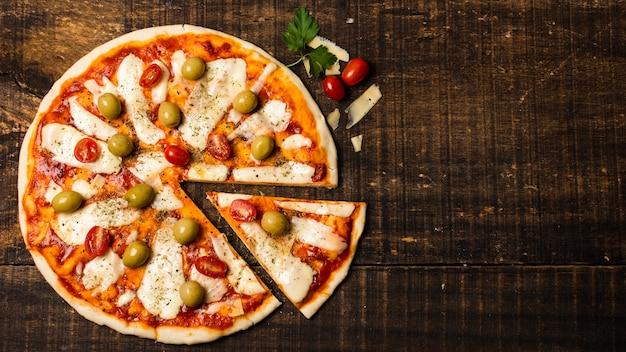 Disposizione piana di pizza sulla tavola di legno