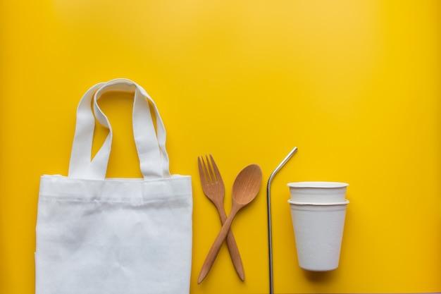 Disposizione piana di prodotti sostenibili, spowooden e paglia inossidabile in sacchetto di stoffa su giallo