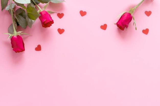 Disposizione piana di san valentino: rose rosse e cuori su uno sfondo rosa con spazio di copia