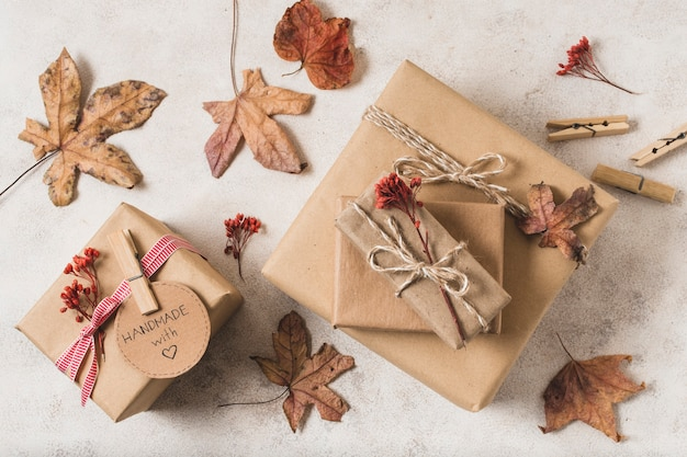 Disposizione piana di scatole regalo con foglie morte e spille per abbigliamento