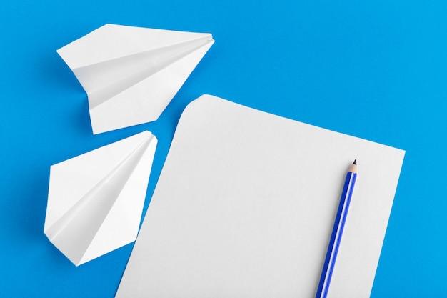 Disposizione piana di un aereo di carta su colore blu pastello