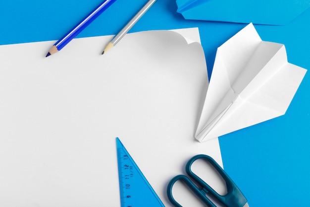 Disposizione piana di un aereo di carta sul fondo di colore blu pastello
