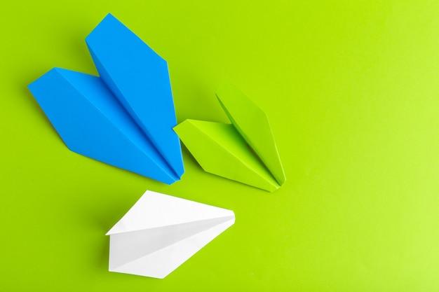 Disposizione piana di un aereo di carta sul fondo verde di colore pastello