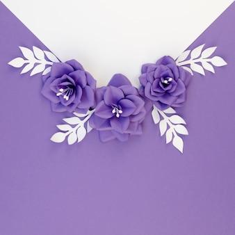 Disposizione piana laica con fiori di carta e sfondo viola