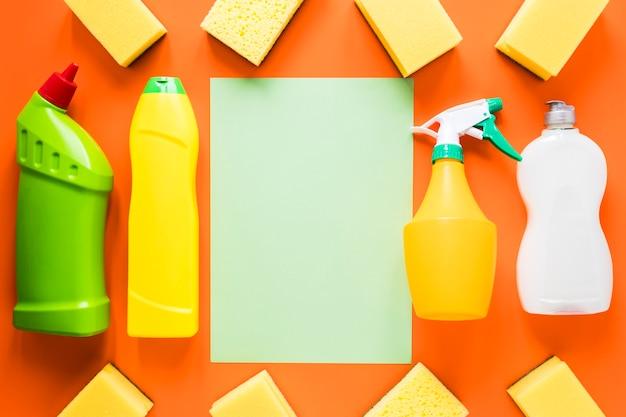 Disposizione piana laica con prodotti per la pulizia su sfondo arancione