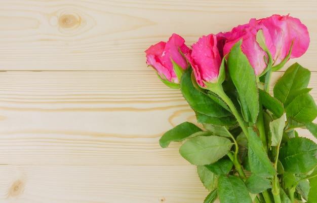 Disposizione piana, rose rosa di vista superiore su fondo di legno beige con lo spazio della copia
