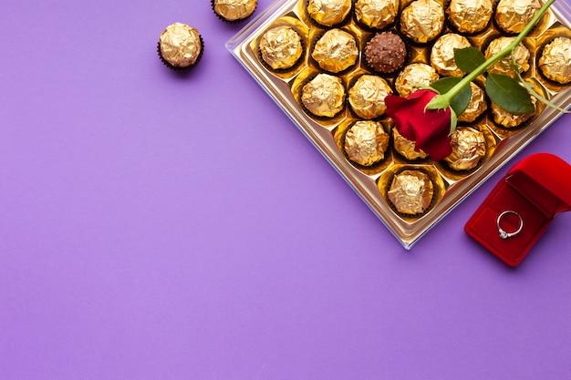 Disposizione piatta con anello, scatola di rose e cioccolato