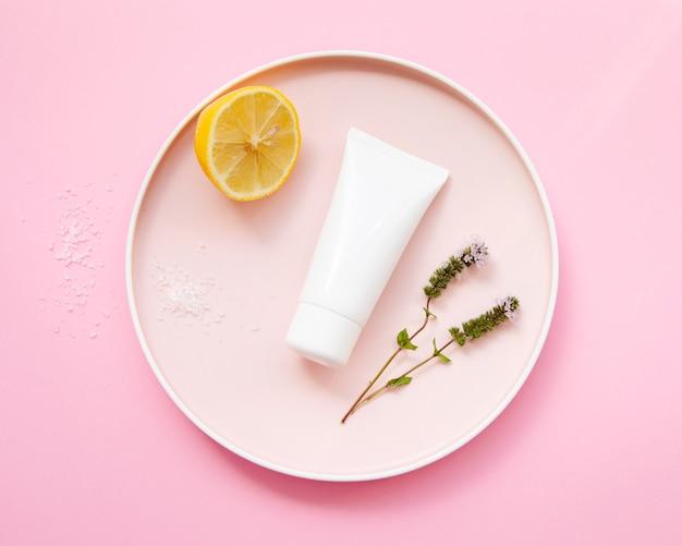 Disposizione piatta con bottiglia di crema e mezzo limone