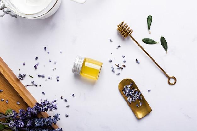 Disposizione piatta con bottiglia di miele e fiori