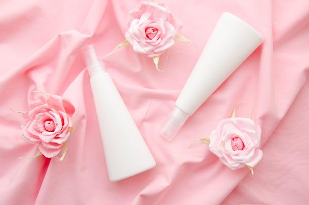 Disposizione piatta con bottiglie bianche e rose