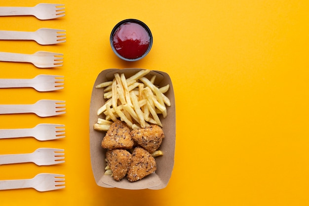 Disposizione piatta con cibo malsano e forchette