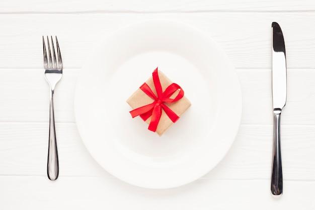 Disposizione piatta con piatto, posate e articoli da regalo