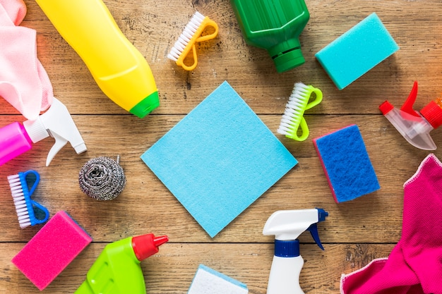 Disposizione piatta con prodotti per la pulizia e fondo in legno