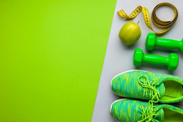 Disposizione piatta con scarpe da ginnastica e manubri