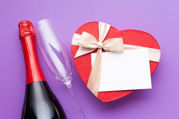 Disposizione piatta con scatola a forma di cuore e vino