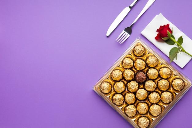 Disposizione piatta con scatola di cioccolatini e rosa