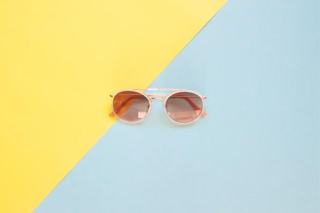 Disposizione piatta creativa degli occhiali da sole alla moda su fondo di tono di colore pastello.