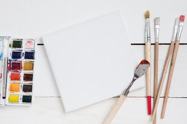 Disposizione piatta degli elementi essenziali della pittura con pennelli e tavolozza