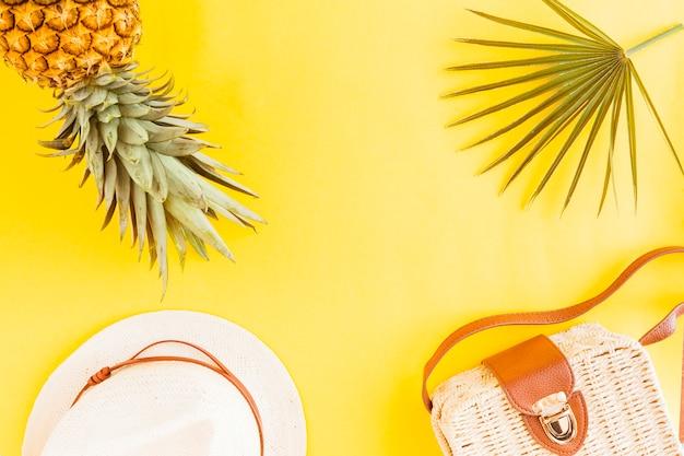 Disposizione piatta di ananas con accessori estivi