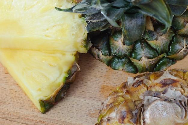 Disposizione piatta di ananas tagliato a fetta. tavolo di legno. vista dall'alto, lavagna luminosa.