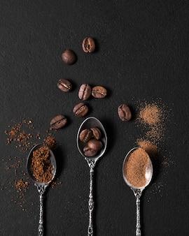 Disposizione piatta di cucchiai ripieni di chicchi di caffè tostati e polvere