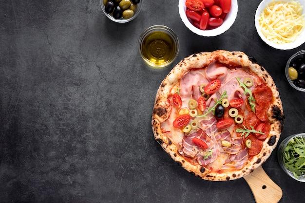 Disposizione piatta di pizza e condimenti