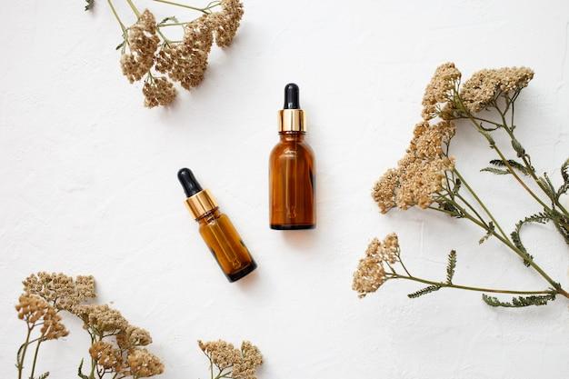 Disposizione piatta di prodotti a base di olio essenziale per la cura della pelle della bottiglia di vetro contagocce per mock up in stile minimal con su sfondo bianco.