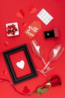 Disposizione piatta laica con cornice e bicchieri su sfondo rosso