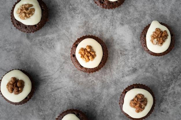 Disposizione piatta laica con cupcakes e sfondo di stucco