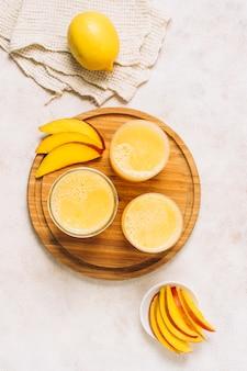 Disposizione piatta laici di frullati freschi accanto al mango a fette