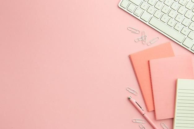 Disposizione piatta sul posto di lavoro rosa con spazio di copia