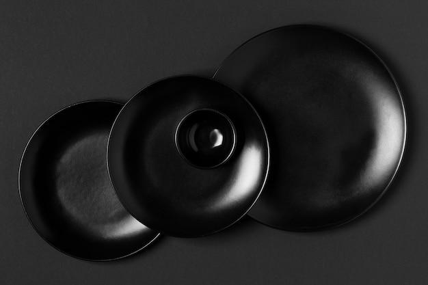 Disposizione piatti neri di diverse dimensioni piatte
