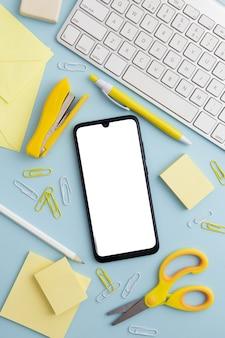 Disposizione stazionaria su sfondo blu con il telefono