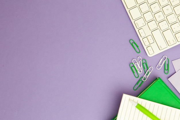 Disposizione sul posto di lavoro su sfondo viola con spazio di copia