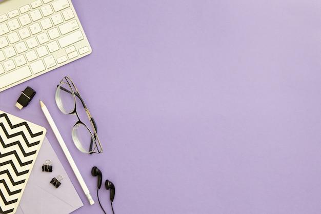 Disposizione sul posto di lavoro vista dall'alto su sfondo viola con spazio di copia