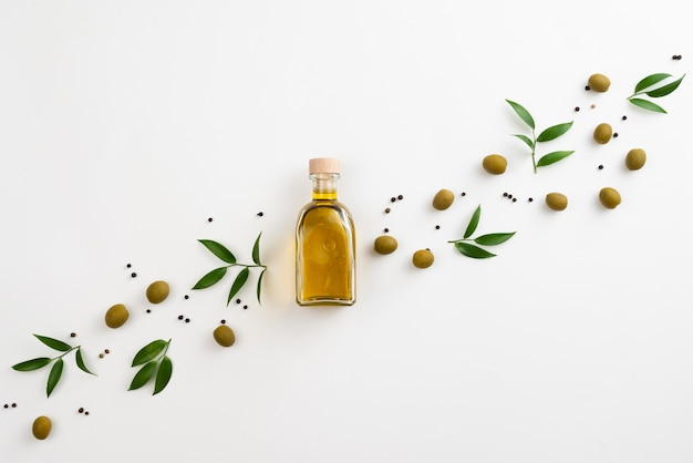 Disposizione sveglia delle foglie e dell'olio d'oliva su fondo bianco