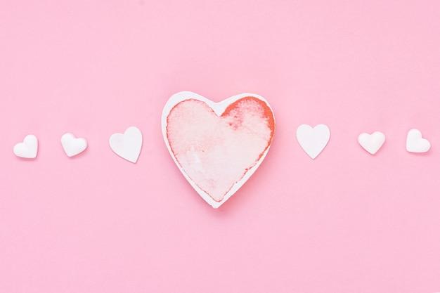Disposizione vista dall'alto con biscotti a forma di cuore e sfondo rosa