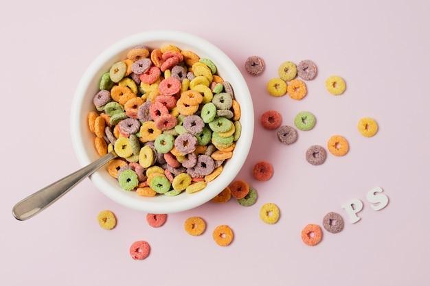 Disposizione vista dall'alto con ciotola di cereali su sfondo rosa
