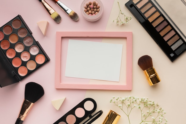 Disposizione vista dall'alto con cosmetici e cornice rosa
