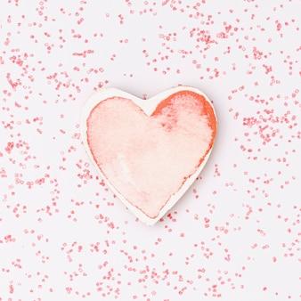 Disposizione vista dall'alto con forma di cuore rosa e sfondo rosa