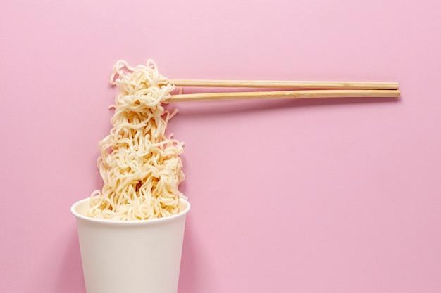 Disposizione vista dall'alto con noodles e sfondo rosa